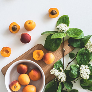 bowl of peaches on a white background